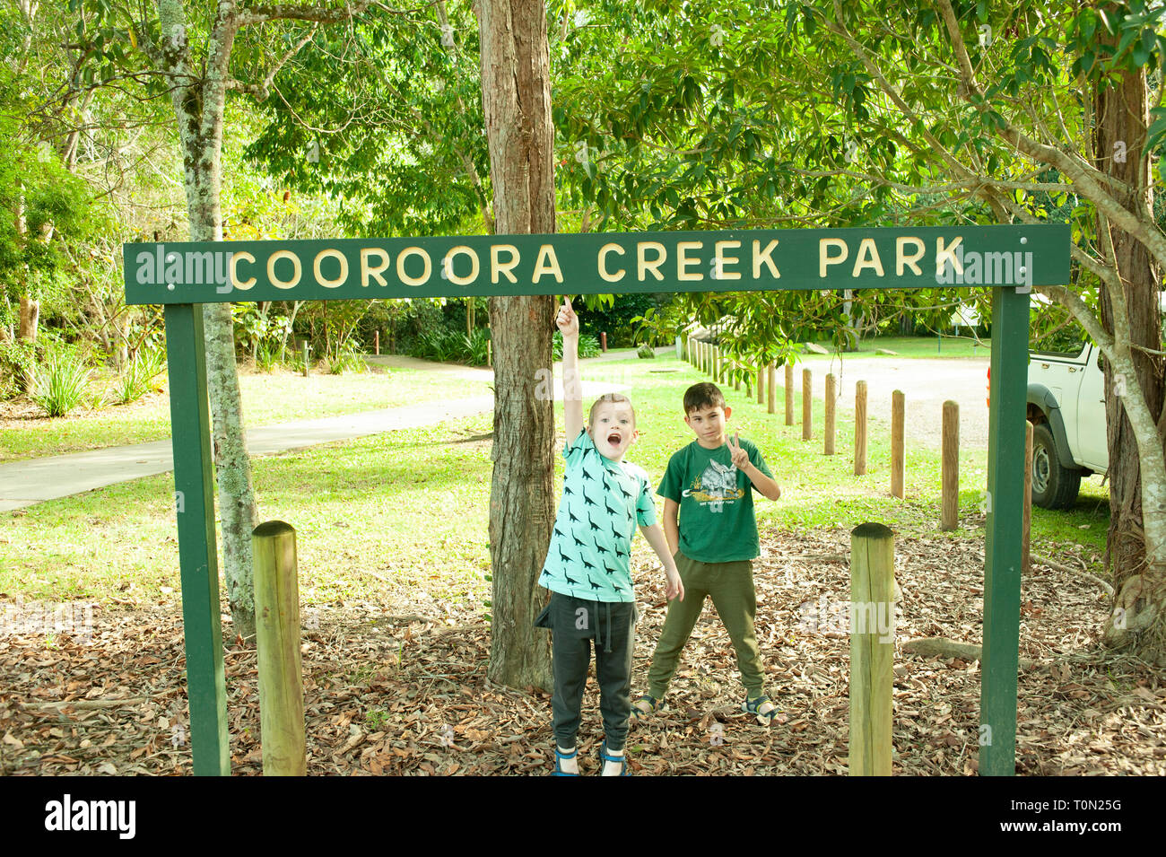 2 young boys stand under a sign at Cooroora Creek Park, Pomona, Queensland, Australia - Stock Image