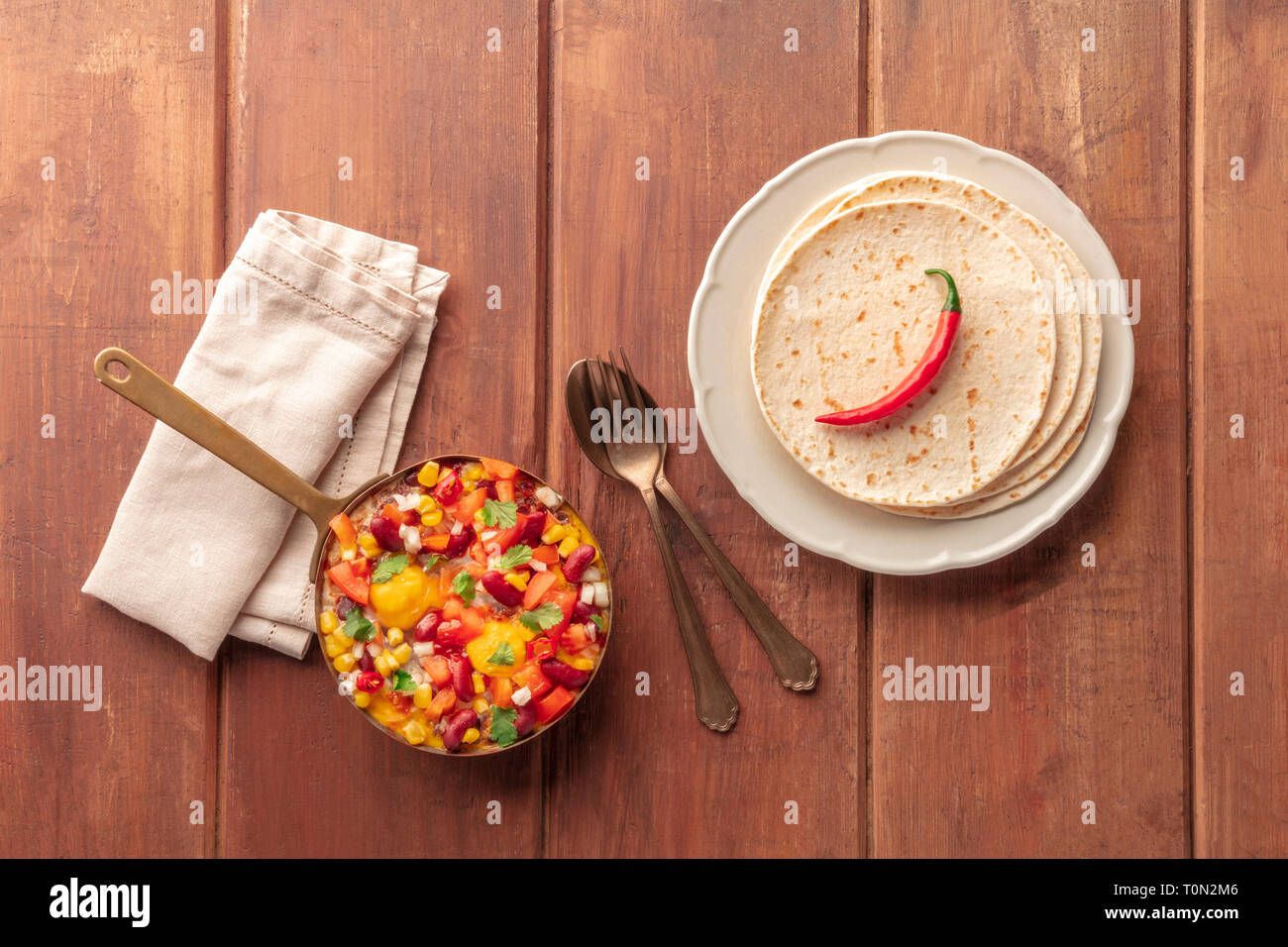 Mexican breakfast. Huevos rancheros, baked eggs, shot from the top with pico de gallo salad, and tortillas on a dark rustic wooden background - Stock Image