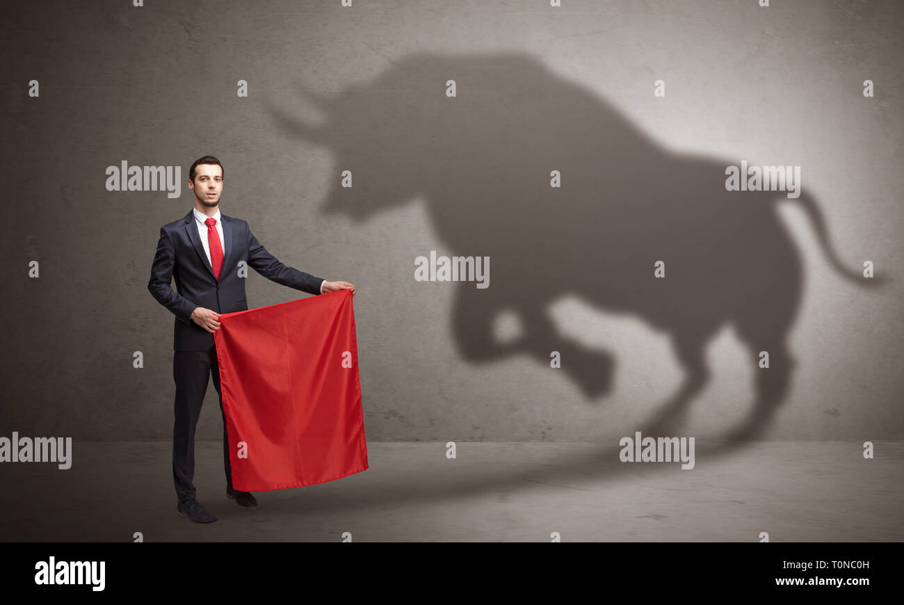 Businessman standing with red cloth in his hand and big bull shadow on the wall  Stock Photo
