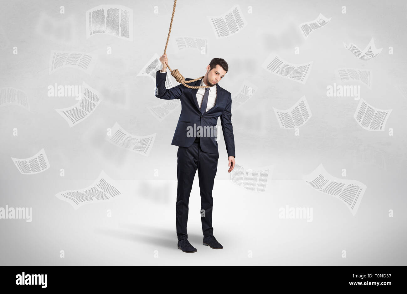 Young burnout businessman with flying documents concept - Stock Image
