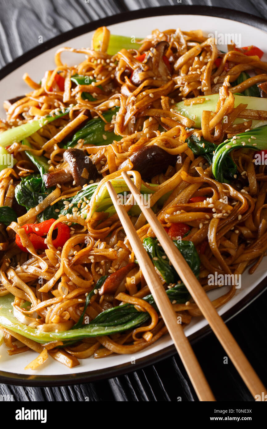 Stir fry of udon noodles with pak choi and shiitake mushrooms close-up on a plate. vertical Stock Photo