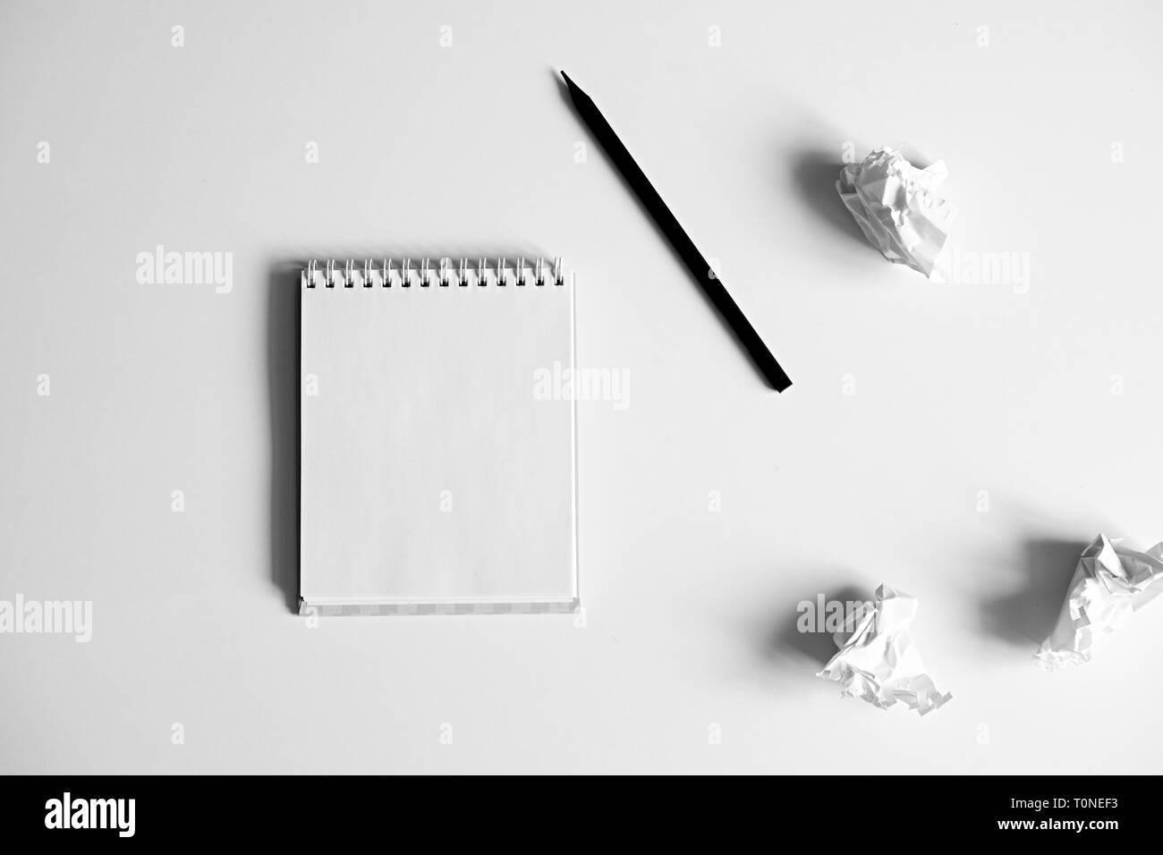Flat lay of blank white notepad, pencil and crumpled paper on white background. Concept of inspiration and lack of ideas. Creativity. - Stock Image