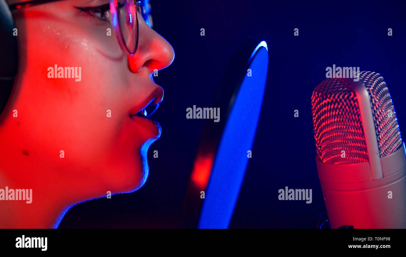A young woman in glasses singing in neon lighting by the microphone Stock Photo
