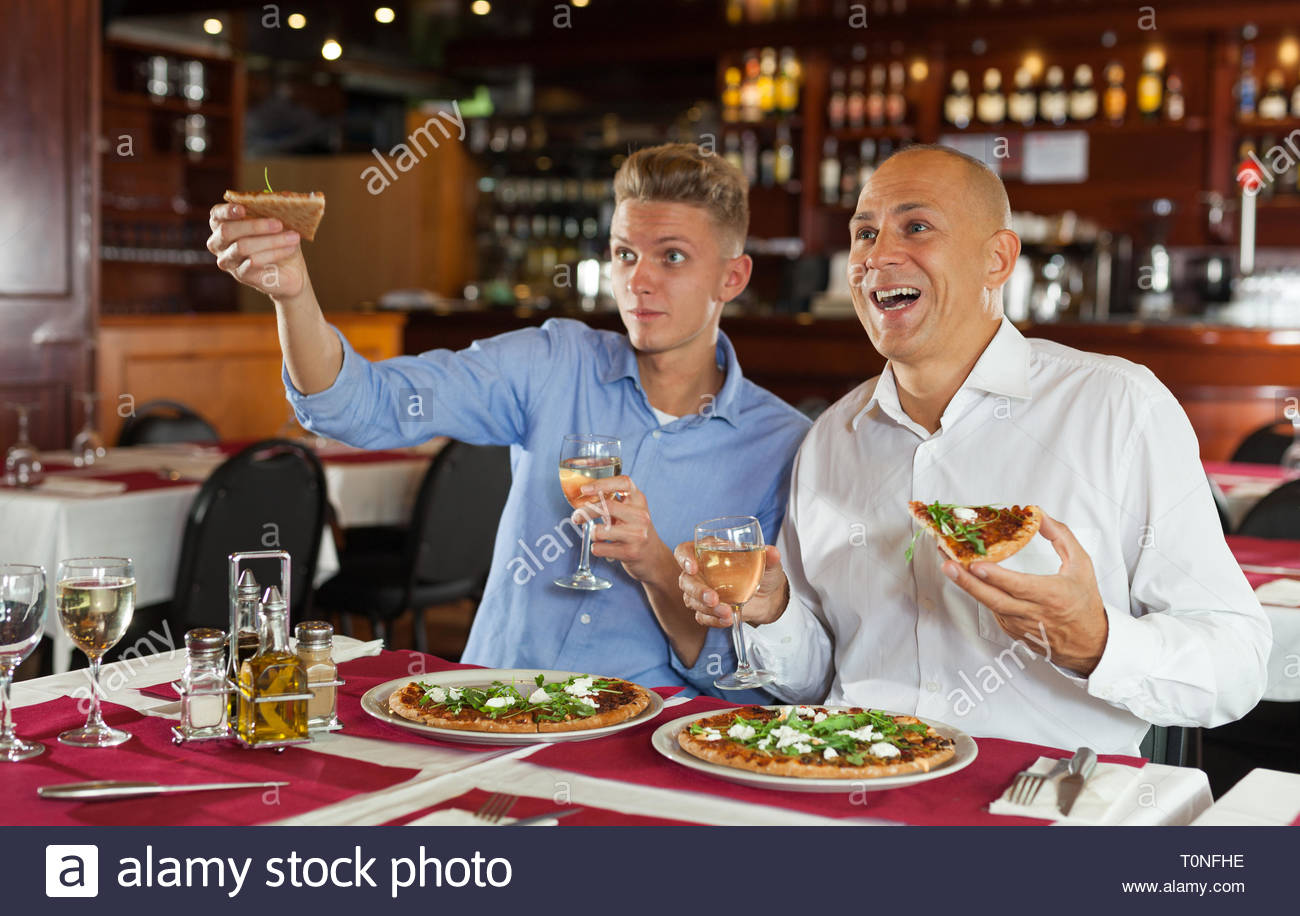Emotional Male Friends Watching Sport Match Together In Restaurant