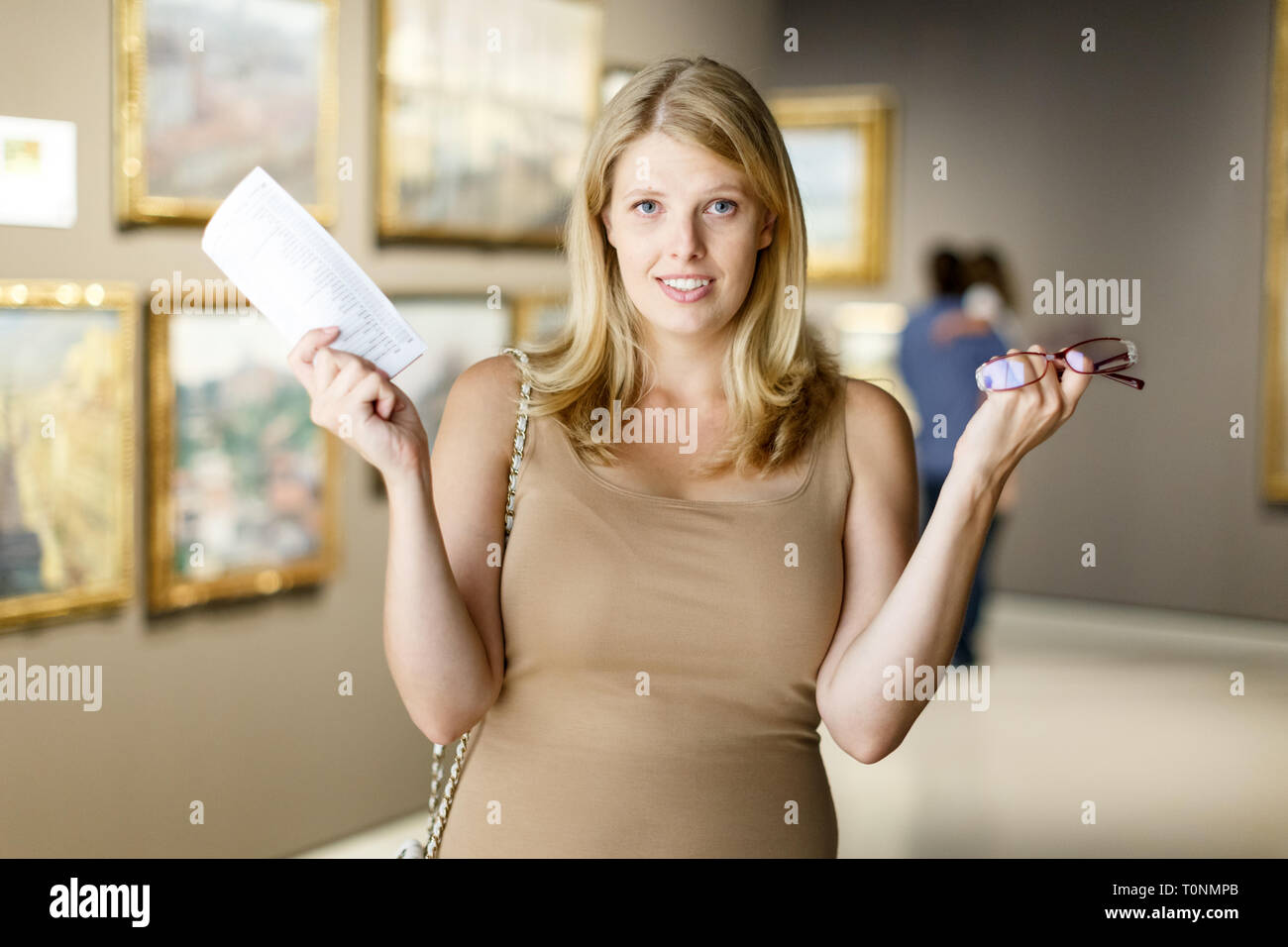 Woman expressing bewilderment standing near picture in art museum - Stock Image