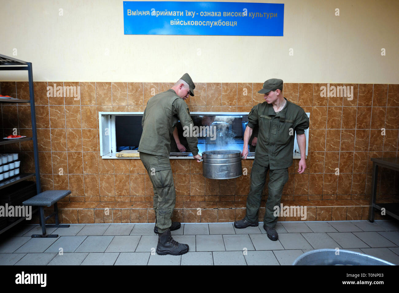 At a chow hall: kitchen workers carrying pot with ready meal for soldiers. Novo-Petrivtsi military base, Ukraine. November 12, 2018 - Stock Image
