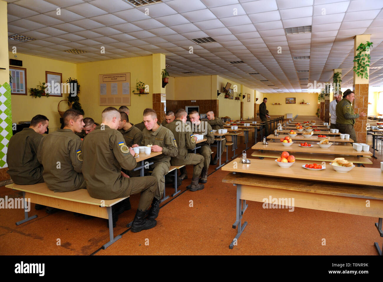 At a mess hall: soldiers sitting at set-out tables and eating. Novo-Petrivtsi military base, Ukraine. November 12, 2018 - Stock Image