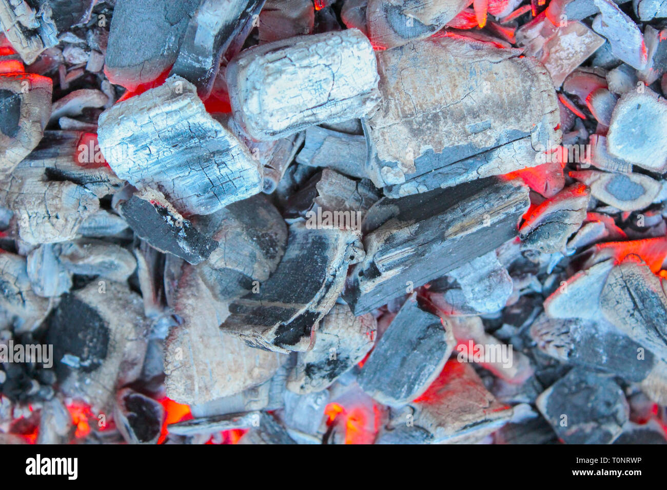 The dying embers in the fire close-up as background - Stock Image