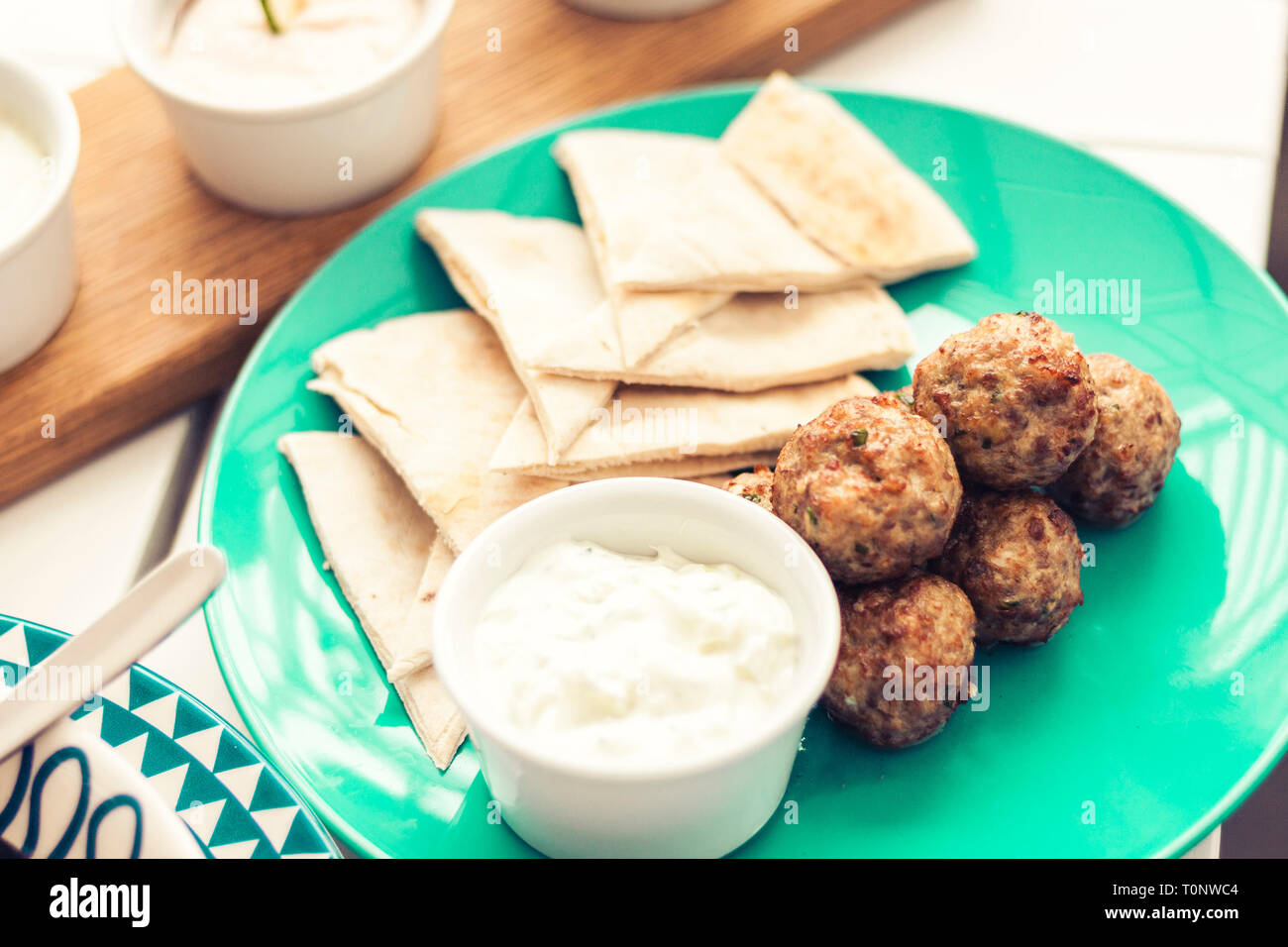 Fried minced meat with sauce and tortillas, traditional Greek lunch on a green plate in a restaurant - Stock Image