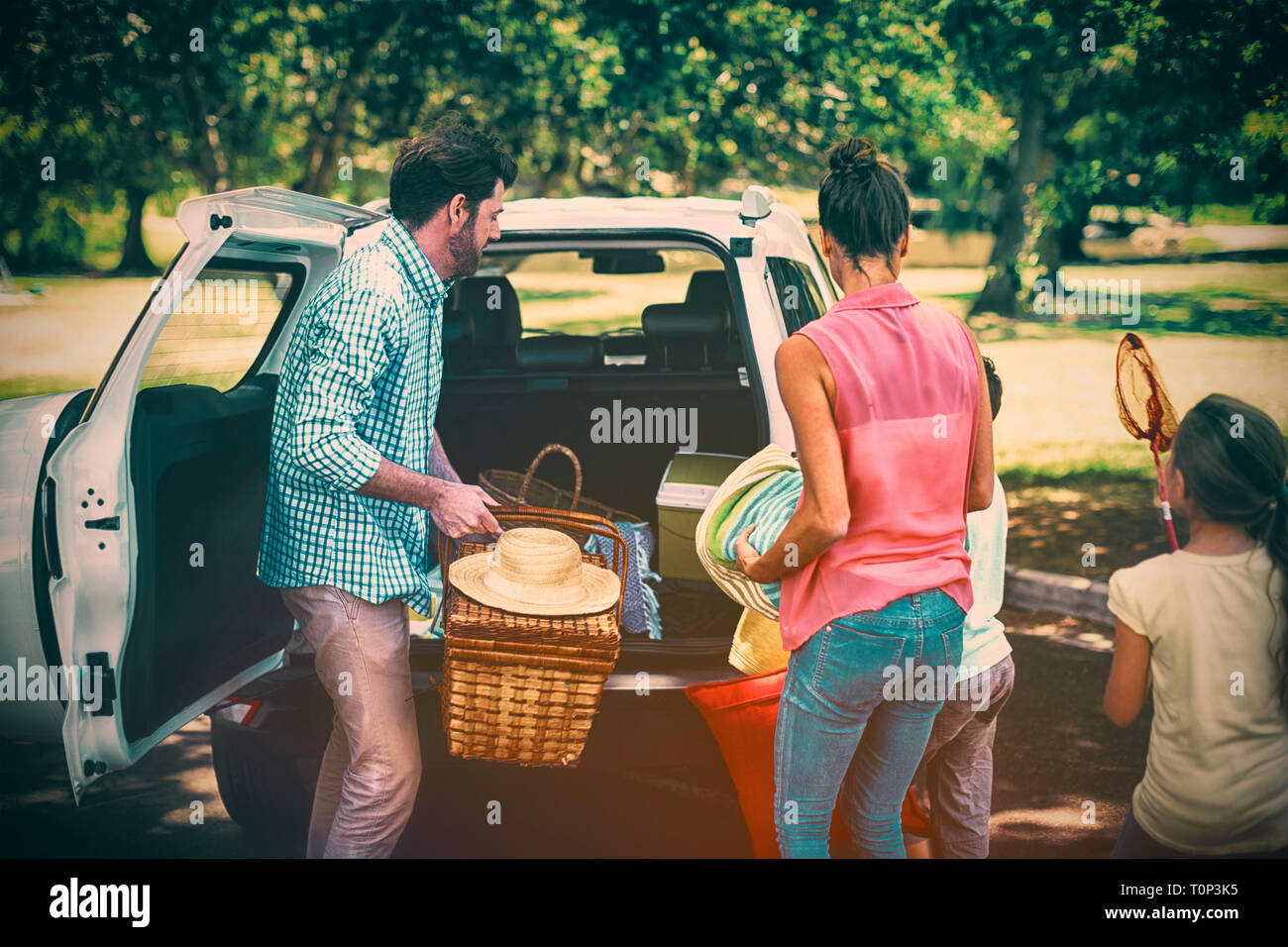 Family placing picnic items in car trunk - Stock Image