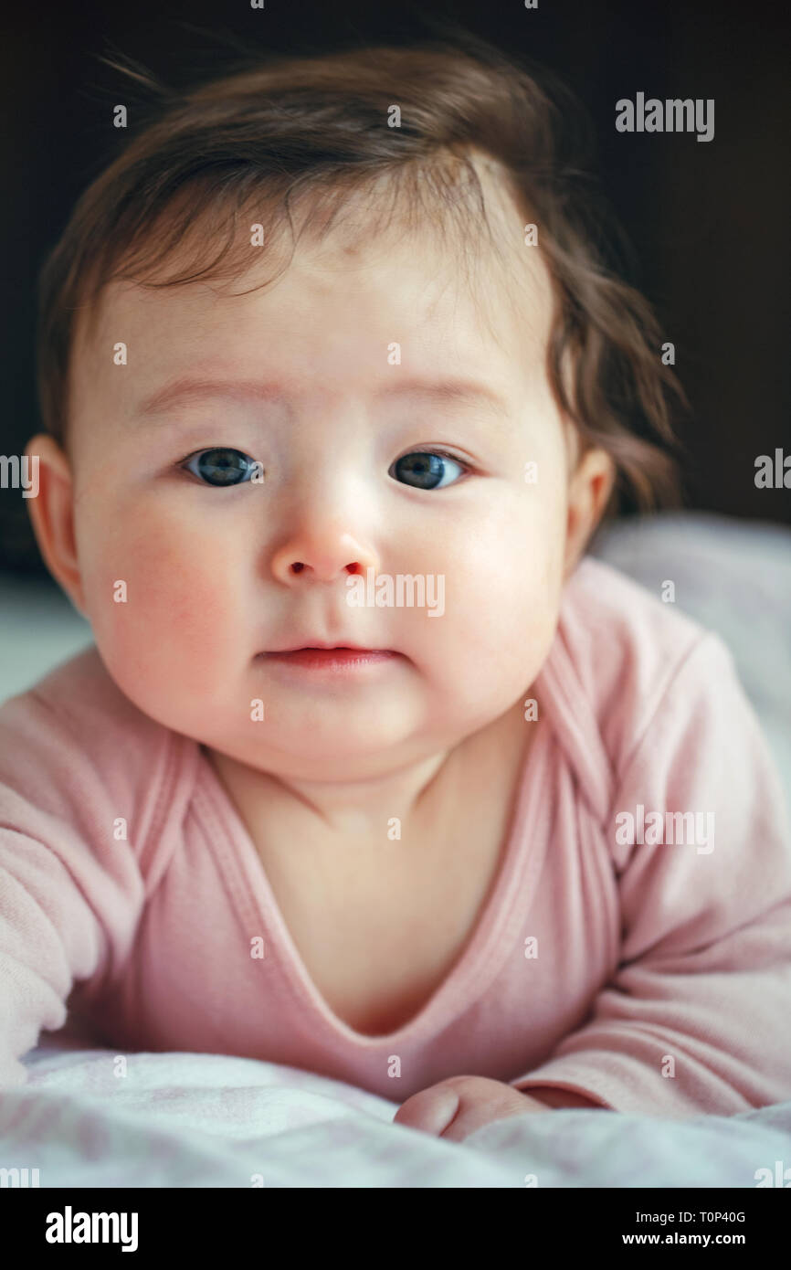 Closeup portrait of cute adorable Asian mixed race baby girl four months old lying on her tummy looking in camera. Natural face expression. Childhood  - Stock Image