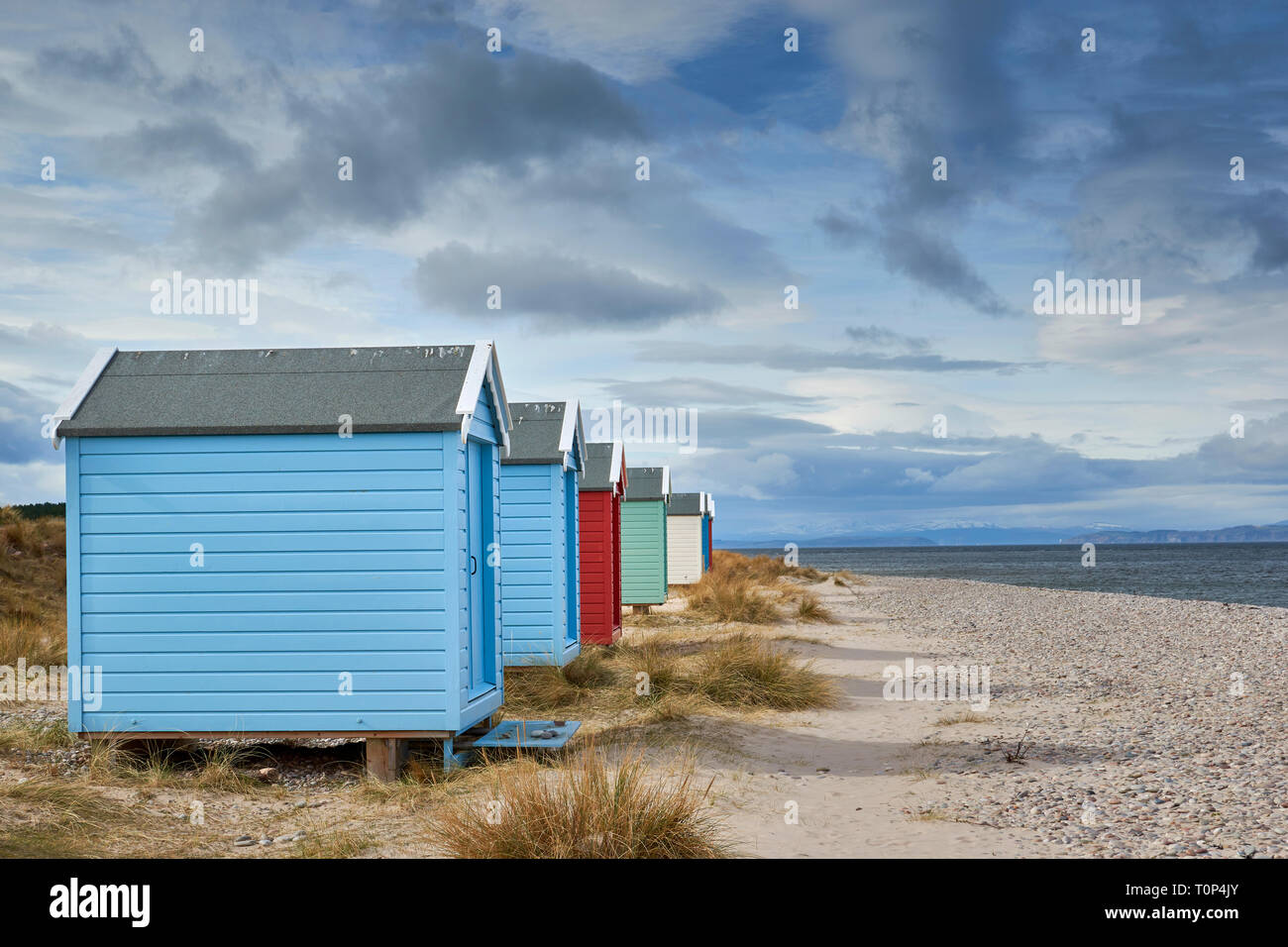 FINDHORN BEACH MORAY FIRTH SCOTLAND PASTEL COLOURED CHALETS OR BEACH HUTS ON PEBBLE BEACH WITH SEA GRASS SNOW OVER THE HILLS AND BLACK ISLE Stock Photo