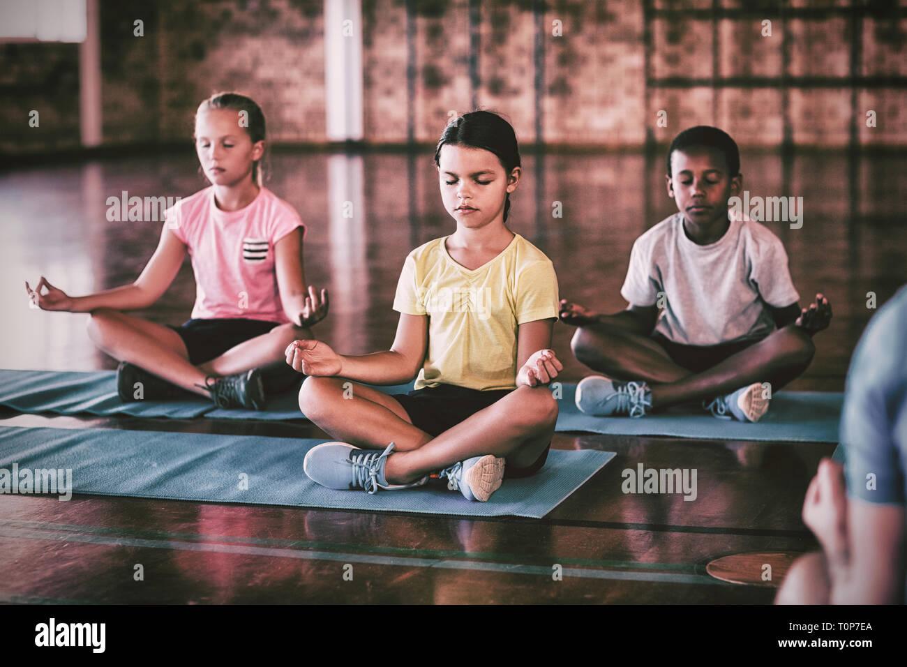 School kids meditating during yoga class Stock Photo