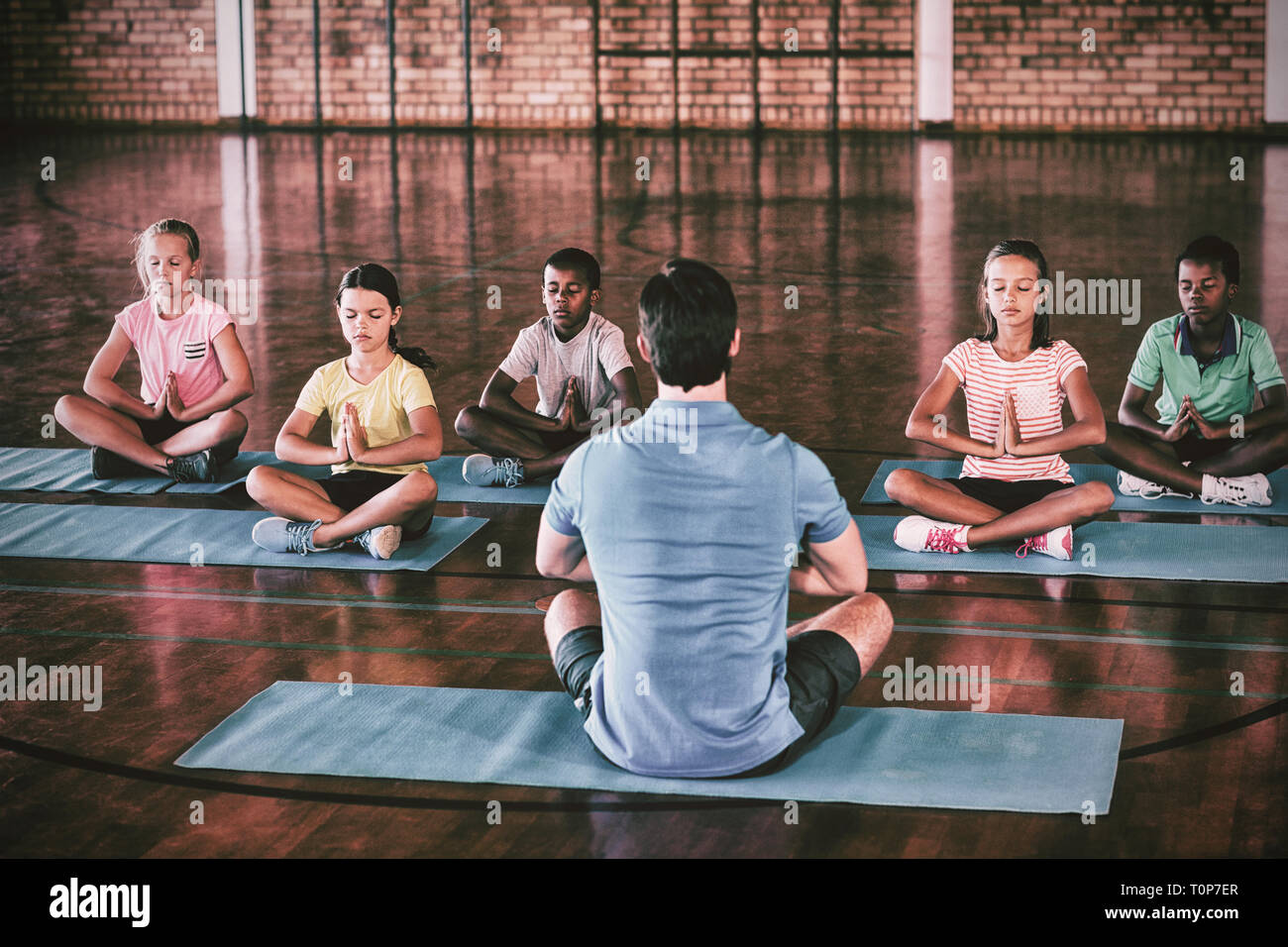 School kids and teacher meditating during yoga class Stock Photo
