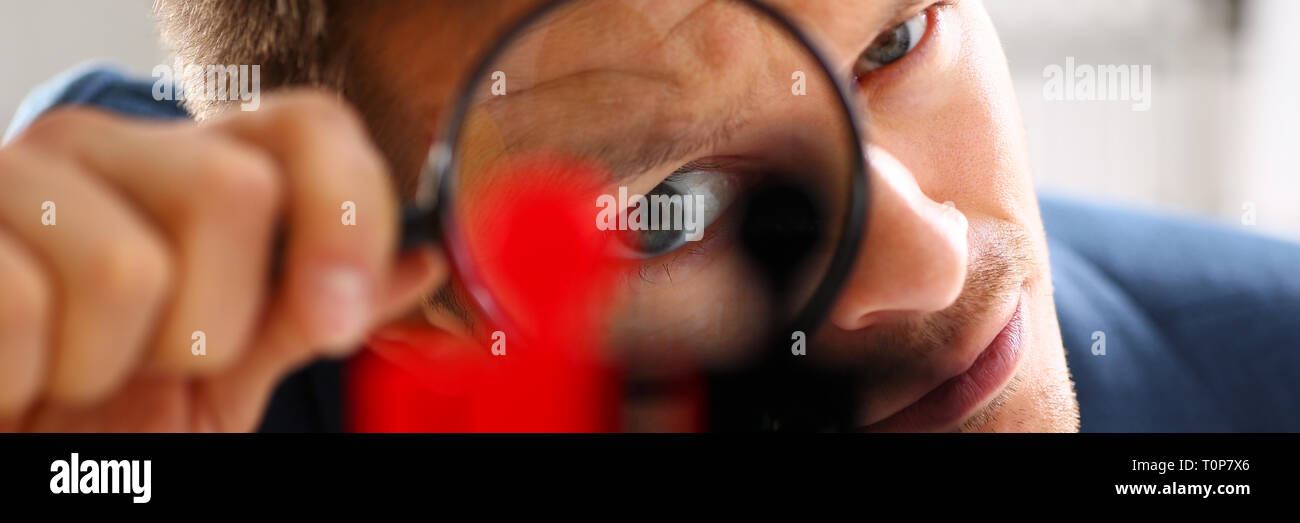Man in suit look thru loupe on statuettes closeup - Stock Image