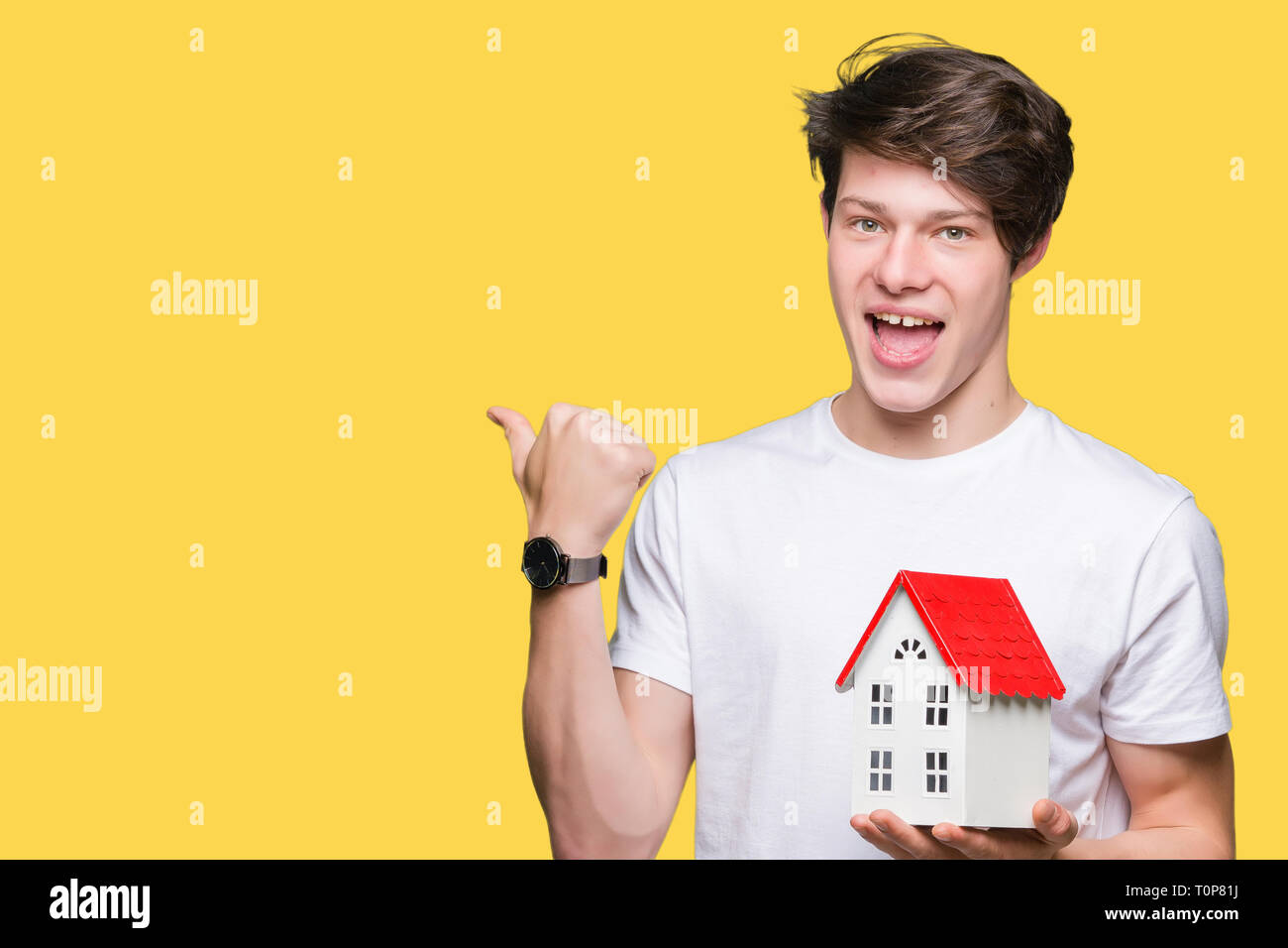 Young man holding house over isolated background pointing and showing with thumb up to the side with happy face smiling - Stock Image