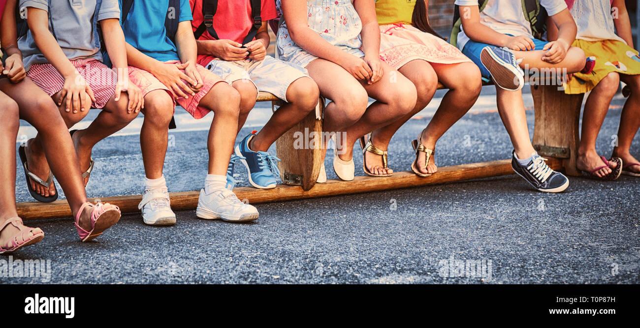 Smiling schoolchildren on seat - Stock Image