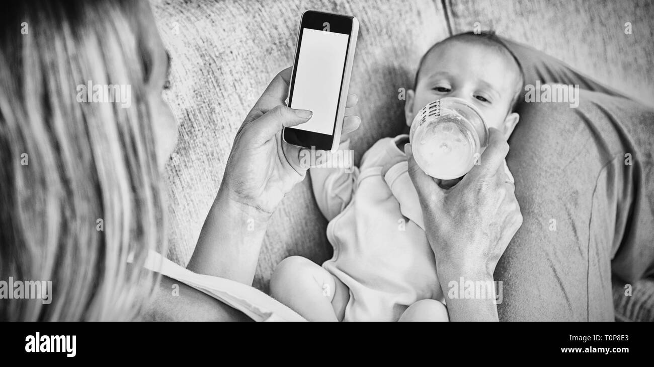 Mother using mobile phone while feeding her baby with milk bottle - Stock Image