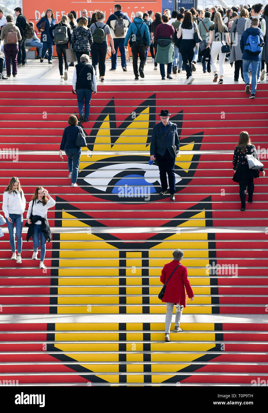 Leipzig, Germany. 21st Mar, 2019. Visitors walk up a staircase in the glass hall, where the logo of the Book Fair can be seen. Until 24.03.2019 about 2600 exhibitors will present themselves on the exhibition grounds. At the same time the festival 'Leipzig reads' invites to numerous readings. The guest country of the Book Fair this year is the Czech Republic. Credit: Jens Kalaene/dpa-Zentralbild/dpa/Alamy Live News - Stock Image