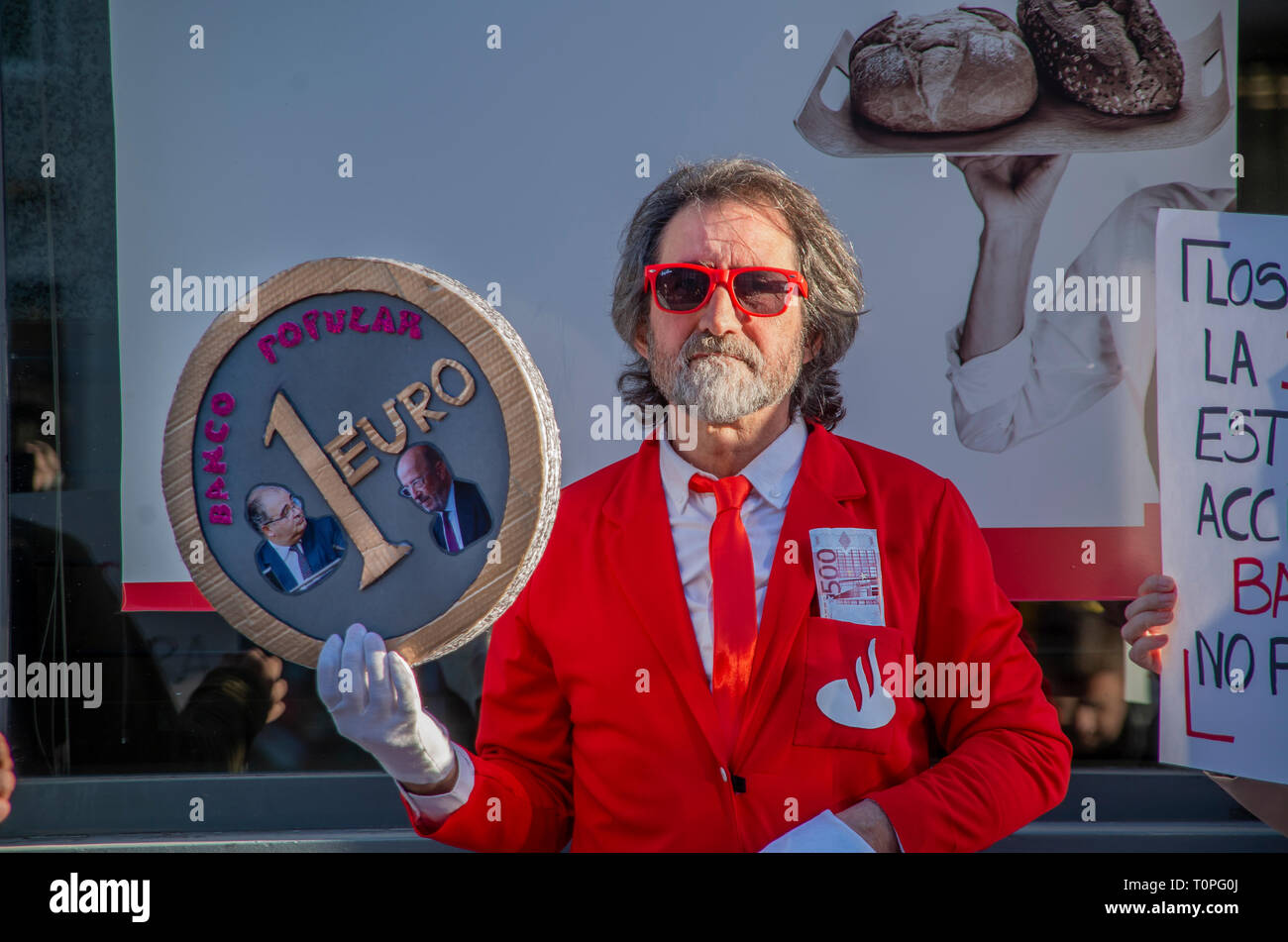 """Madrid, Spain. 21st Mar 2019. Scammed shareholders protested in front of the bank """"Banco Popular"""" part of Santander Group in Madrid. Some 300 000 shareholdres have been left with no money in their accounts.  In the picture, a man disguised as a bank worker holding a huge euro coin that says """"Banco Popular"""" Credit: Lora Grigorova/Alamy Live News - Stock Image"""