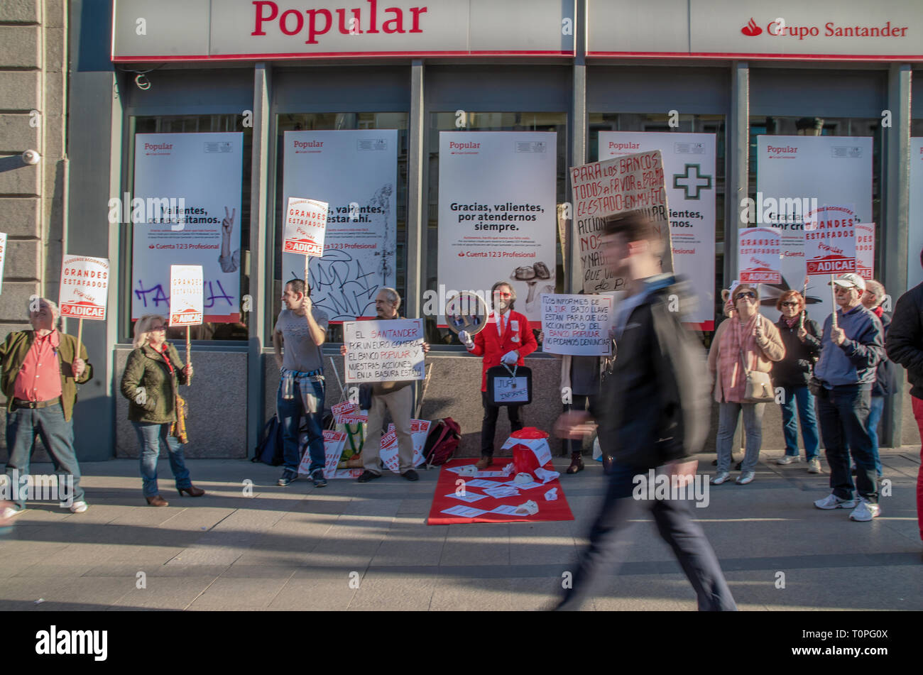 """Madrid, Spain. 21st Mar 2019. Scammed shareholders protested in front of the bank """"Banco Popular"""" part of Santander Group in Madrid. Some 300 000 shareholdres have been left with no money in their accounts.  In the picture, people protesting with placards in font of the bank. Credit: Lora Grigorova/Alamy Live News - Stock Image"""