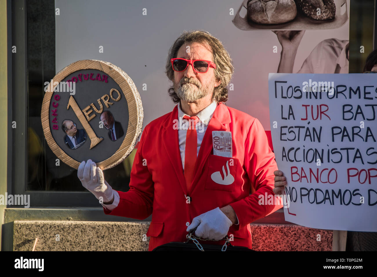 A man with suite of santander bank a nd in one of their hands a euro palacard with a picture of executives of the popular bank.  Demonstration against the popular bank, of the group of Santander bank by the small shareholders swindled in the year 2018. 305,000 shareholders lost all their money for the bankrupt of the popular bank. executed by the fraud of the group of Emilio Saracho with the bank of Spain. Credit: Alberto Sibaja Ramírez/Alamy Live News - Stock Image