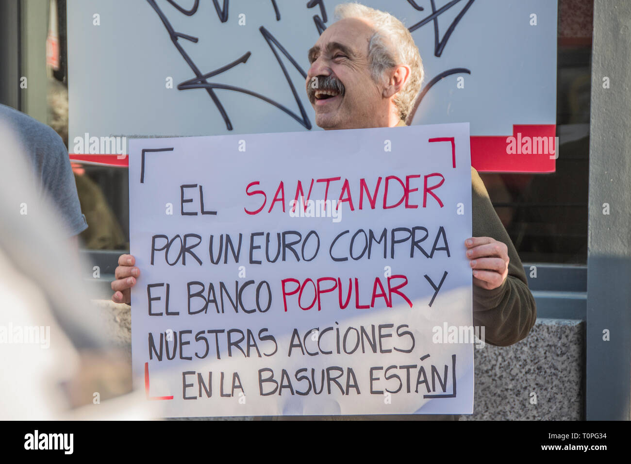 A man with a placard with the motto  Santander bank for one euro buys the popular bank and our shares in the trash are. Demonstration against the popular bank, of the group of Santander bank by the small shareholders swindled in the year 2018. 305,000 shareholders lost all their money for the bankrupt of the popular bank. executed by the fraud of the group of Emilio Saracho with the bank of Spain. Credit: Alberto Sibaja Ramírez/Alamy Live News - Stock Image