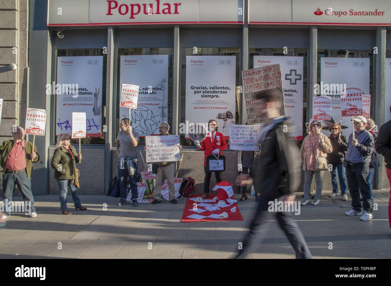 March 21, 2019 - Madrid, Madrid, Spain - Protesters are seen holding placards in font of the bank during the demonstration..Scammed shareholders protested in front of the Banco Popular bank part of Santander Group in Madrid. Some 300,000 shareholders have been left with no money in their accounts. (Credit Image: © Lora Grigorova/SOPA Images via ZUMA Wire) - Stock Image