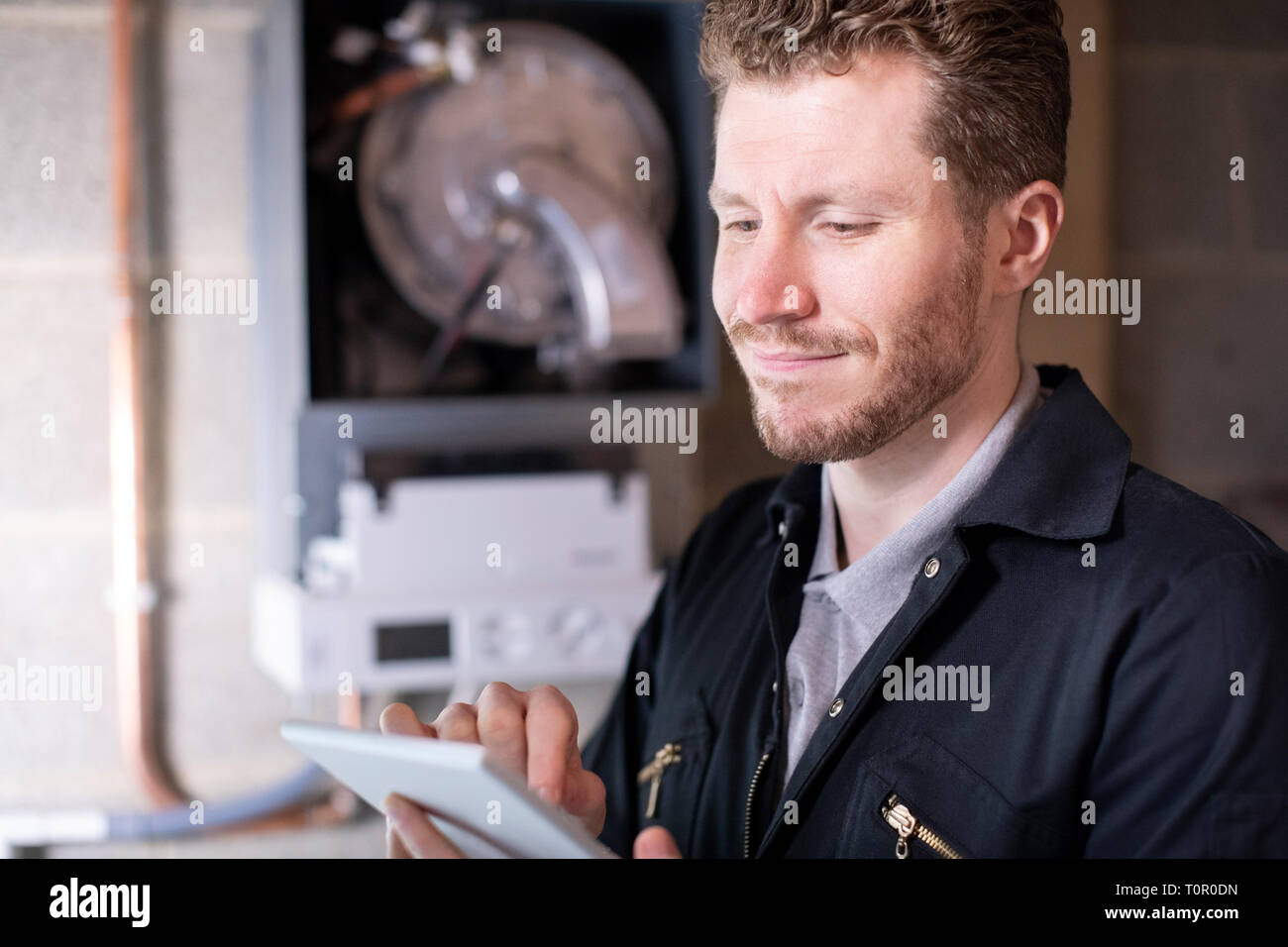 Male Heating Engineer Servicing Central Heating Boiler Using Digital Tablet - Stock Image
