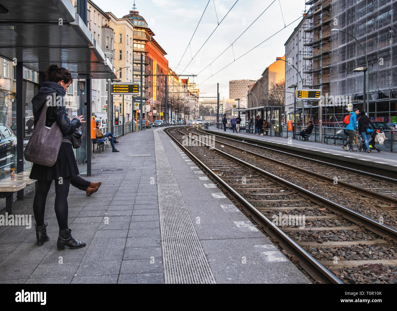 Berlin-Mitte. Rosa-Luxemburg-Platz U-Bahn tram stop with platform, people waiting and tram lines - Stock Image