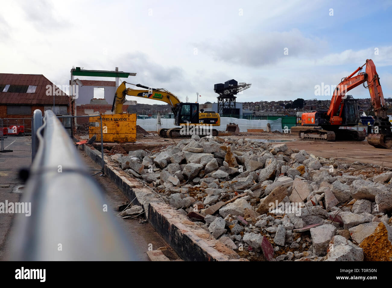 view,over,fence,of,demolition,site,building,diggers,factory,warehouse,concrete,debris,bricks,roof,East Cowes, Isle of Wight,England,UK, - Stock Image