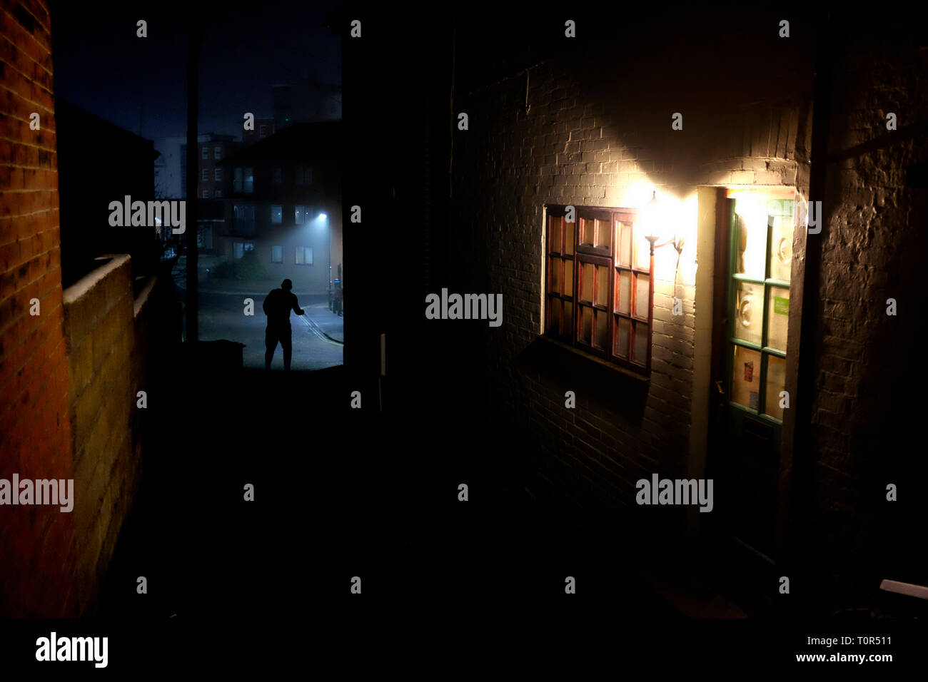 sinister,figure,in,silhouette,silhouetted,at,end,of,alleyway,alley,house,lights,front,door,criminal,crime,murder,murderer,fear,of,night,dark,shadows,l - Stock Image