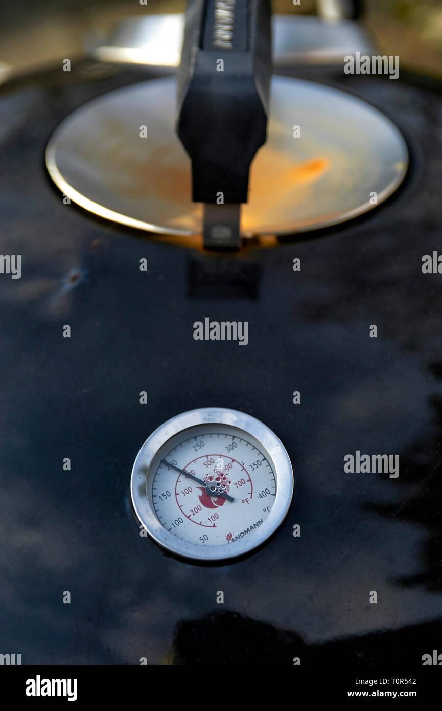Temperaturanzeige eines Kugelgrills im Deckel mit Handgriff. Das Termomether zeigt 200 C° Stock Photo