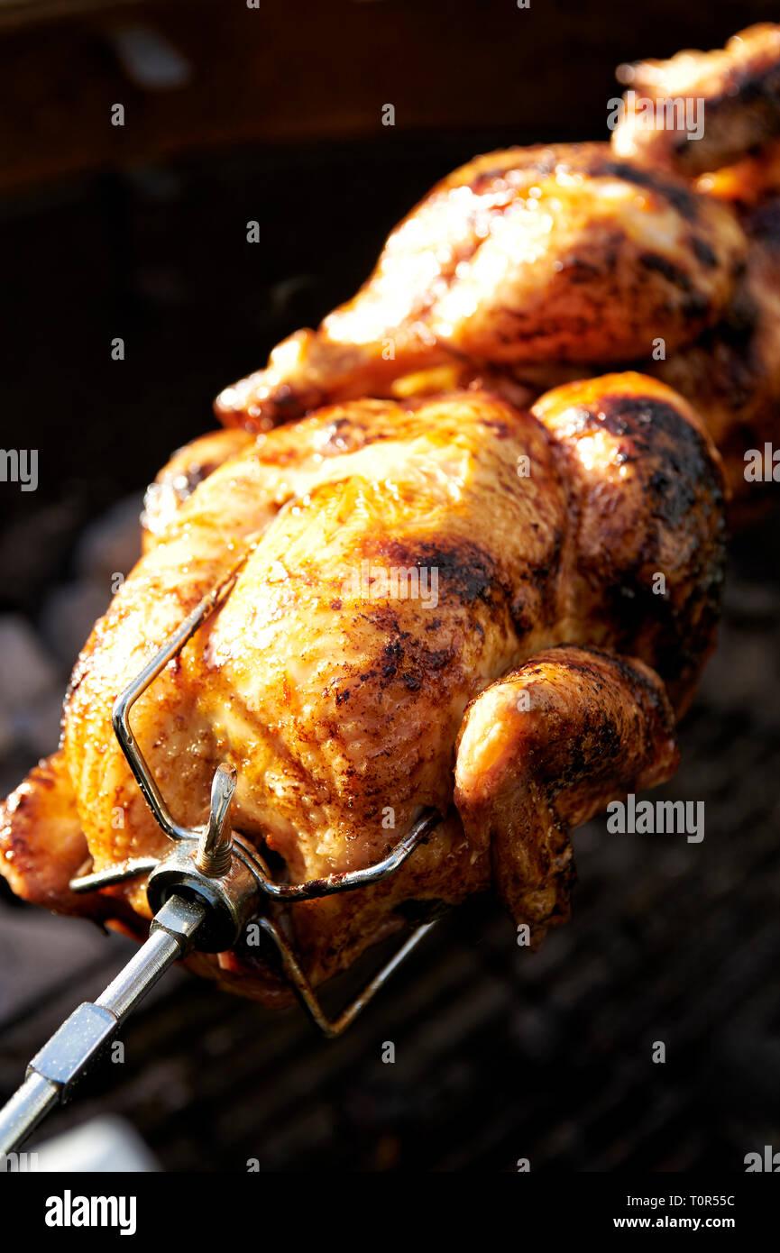 Grillen mit Gefluegel: Auf einem Grillspiess drehen sich zwei Grillhaenchen ueber dem Grill. - Stock Image