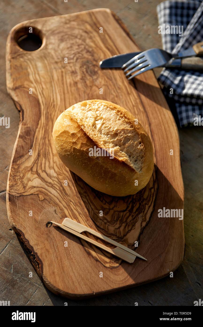 Ein Weizenbroetchen liegt auf einem Holzbrettchen und wartet darauf belegt zu werden. Als Deko liegt Messer und Gabel daneben, sowie Holzspiesschen - Stock Image