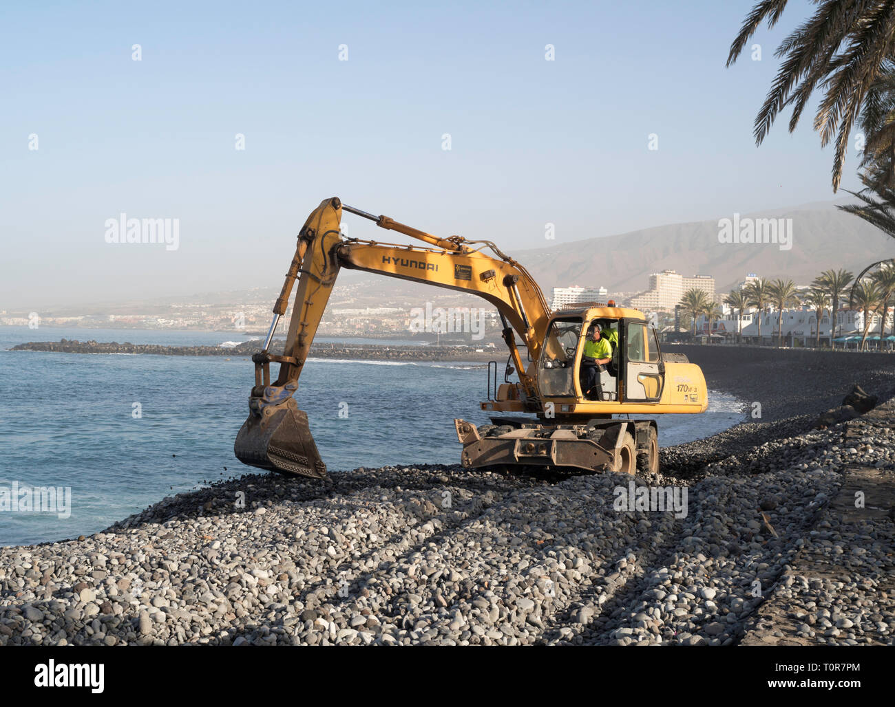 Hyundai R 170 W wheeled excavator maintaining sea defences in Costa Adeje, Tenerife, Canary Islands. - Stock Image