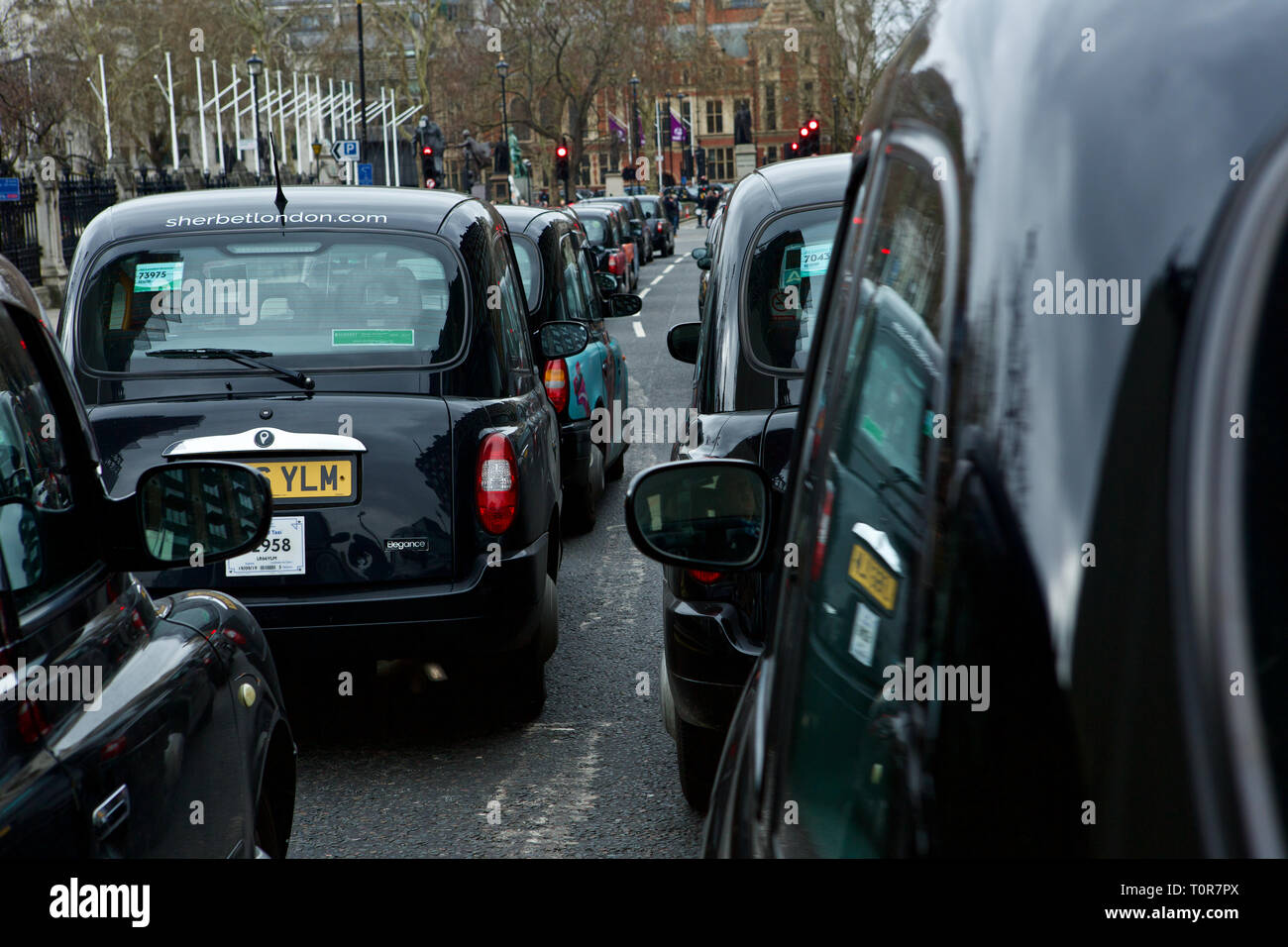 Black cab drivers block Parliament Square, Westminster Bridge and part of whitehall in protest at Sadiq Khan's plans to improve air quality. - Stock Image