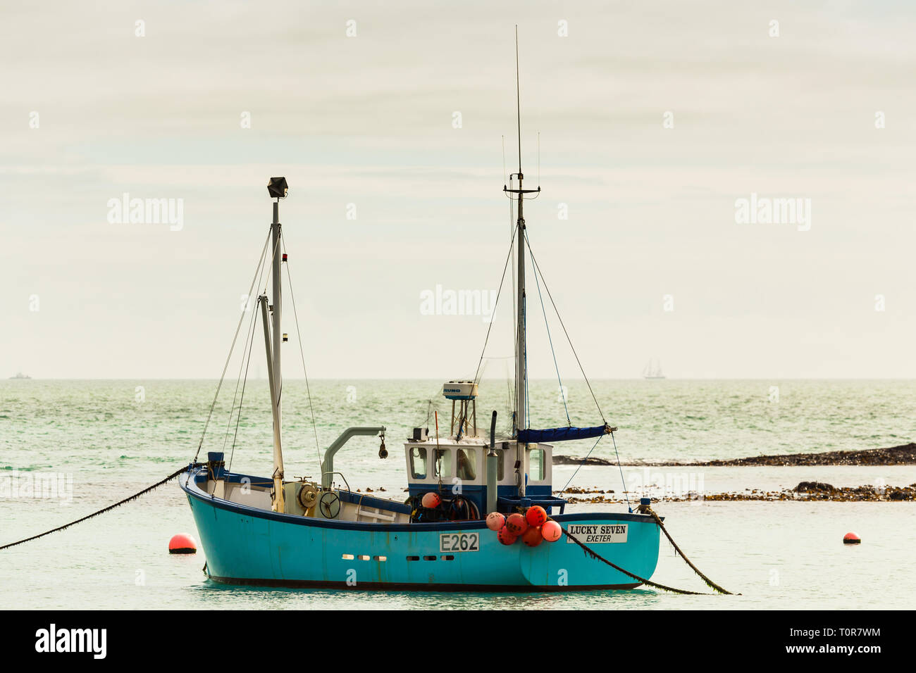 Looking out to sea at Lulworth Cove a fishing vessel is anchored in the Bay. - Stock Image