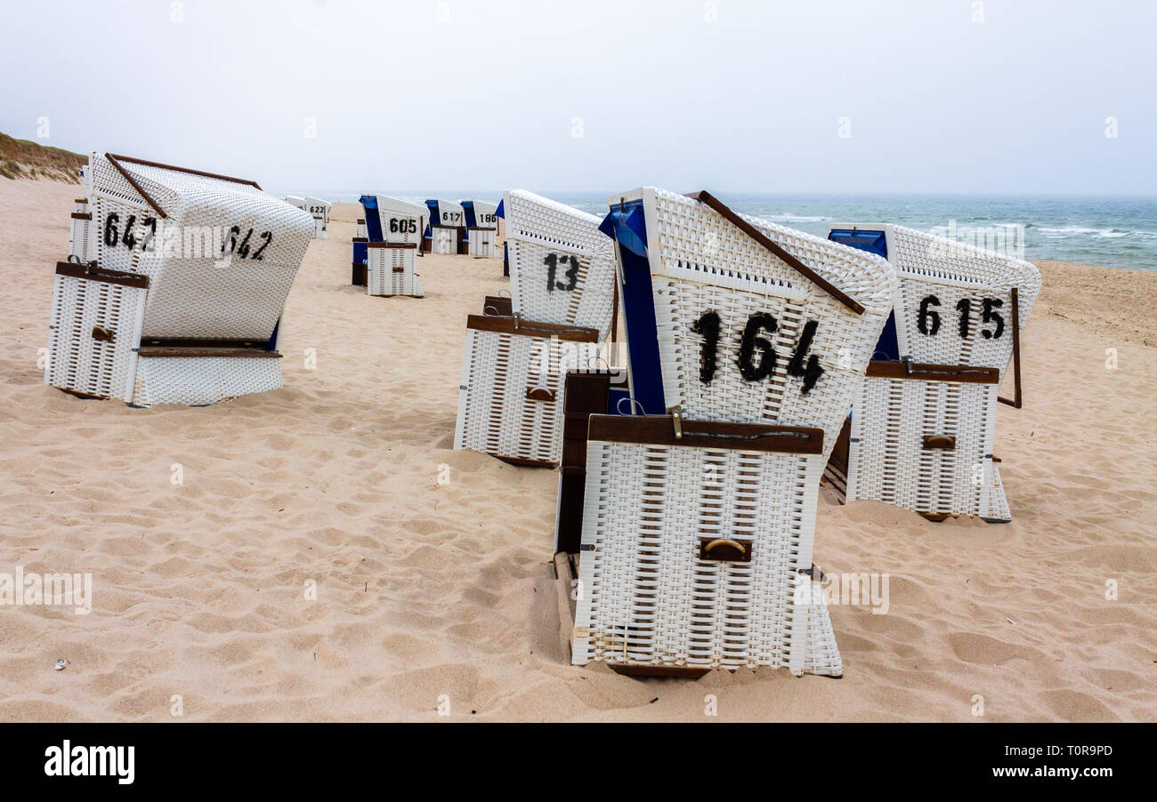 Row of roofed wicker beach chairs in a dune landscape. Located in Hörnum auf Sylt, Schleswig-Holstein, Germany. Europe Stock Photo