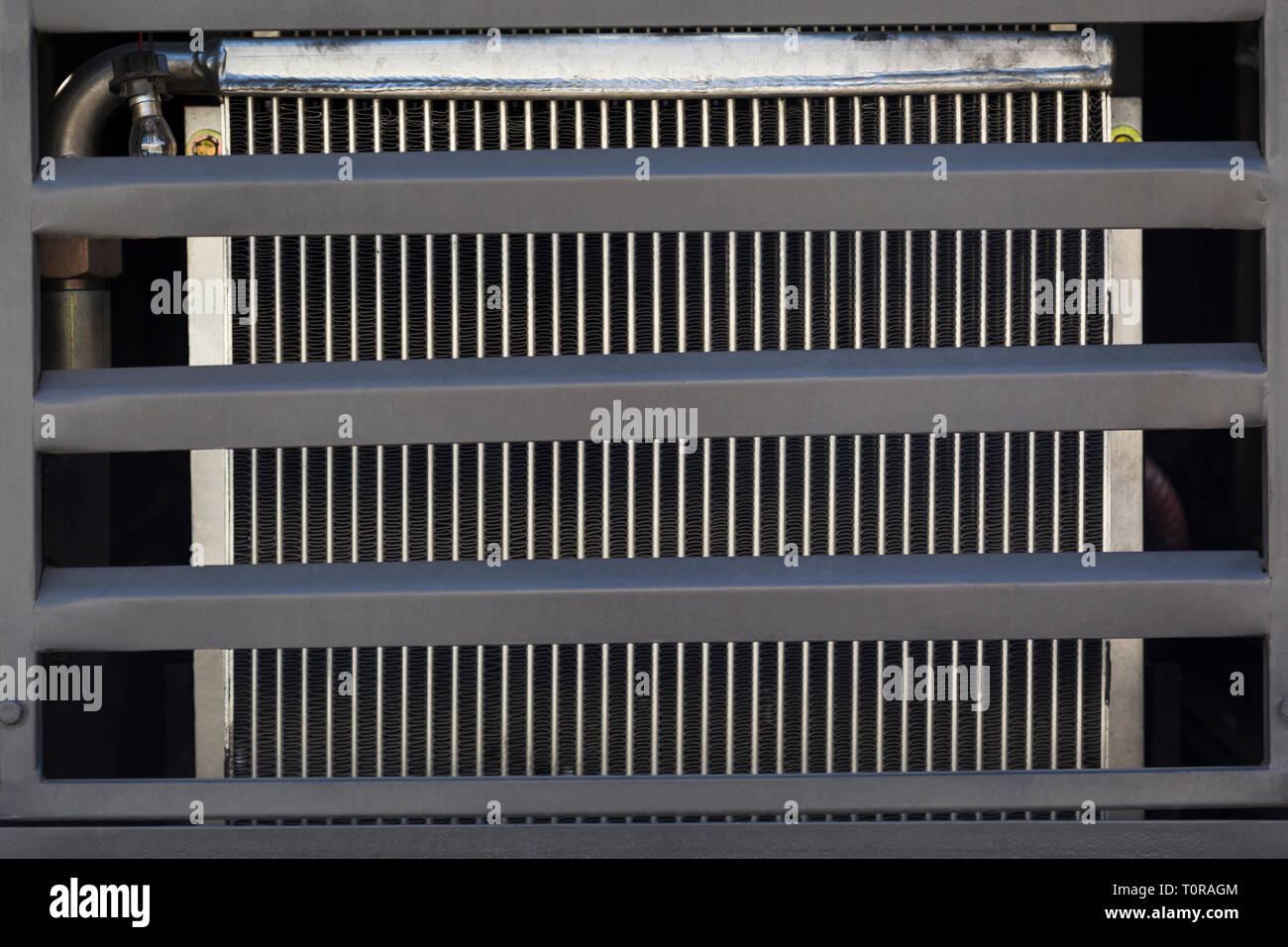 Radiator cooling the engine of the road machinery, stained with soot, closed with a gray metal protective grille, close-up - Stock Image