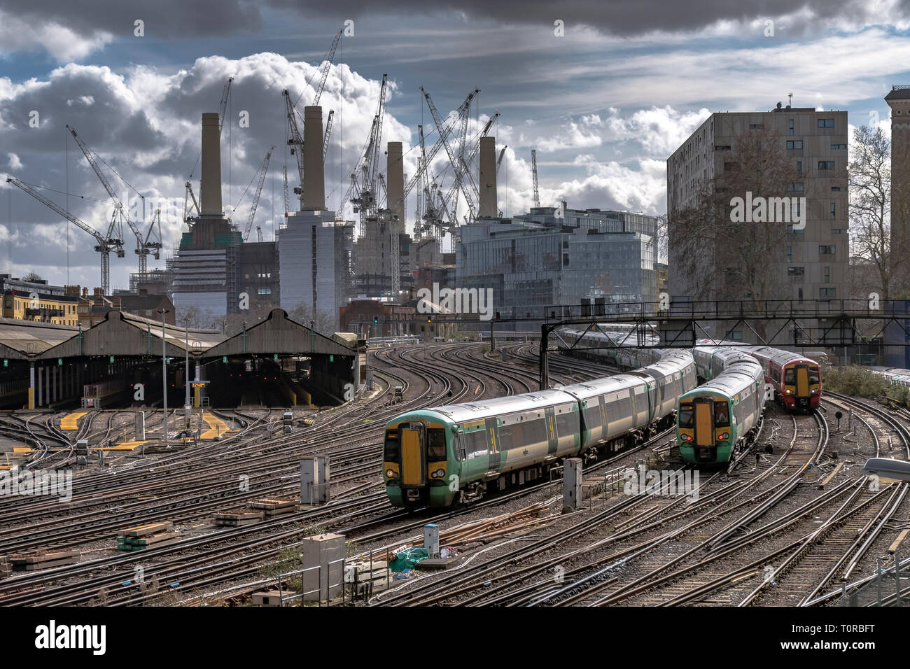 Southern Rail train approaching Ebury Bridge on the final approach to Victorian Station ,with Battersea Power Station in the distance ,London SW1 - Stock Image