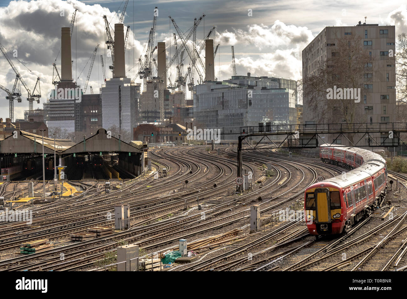 The Gatwick Express approaching Ebury Bridge on the final approach to Victorian Station ,with Battersea Power Station in the distance ,London SW1 - Stock Image