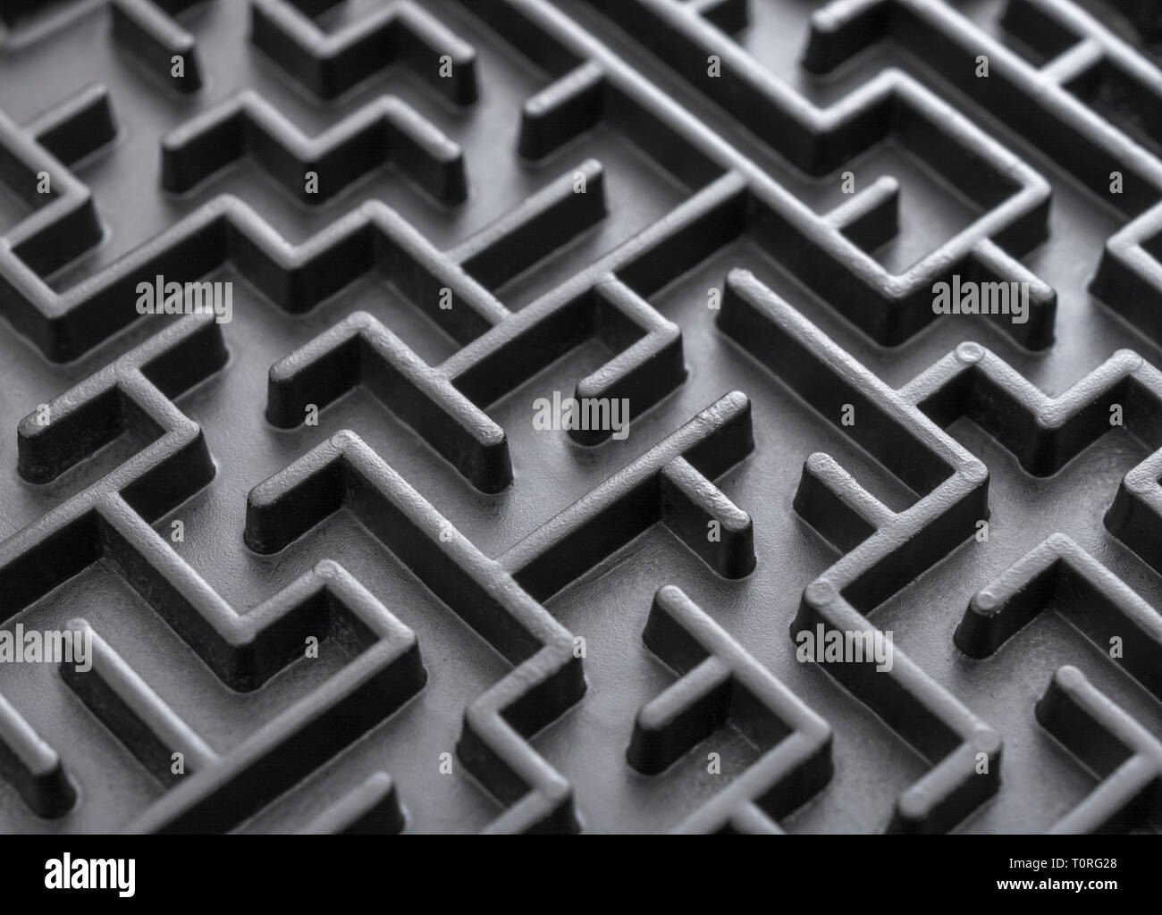 Macro shot of small toy maze painted black. Metaphor for complex, getting lost, navigating, problem solving, unreachable goals, Brexit talks. - Stock Image