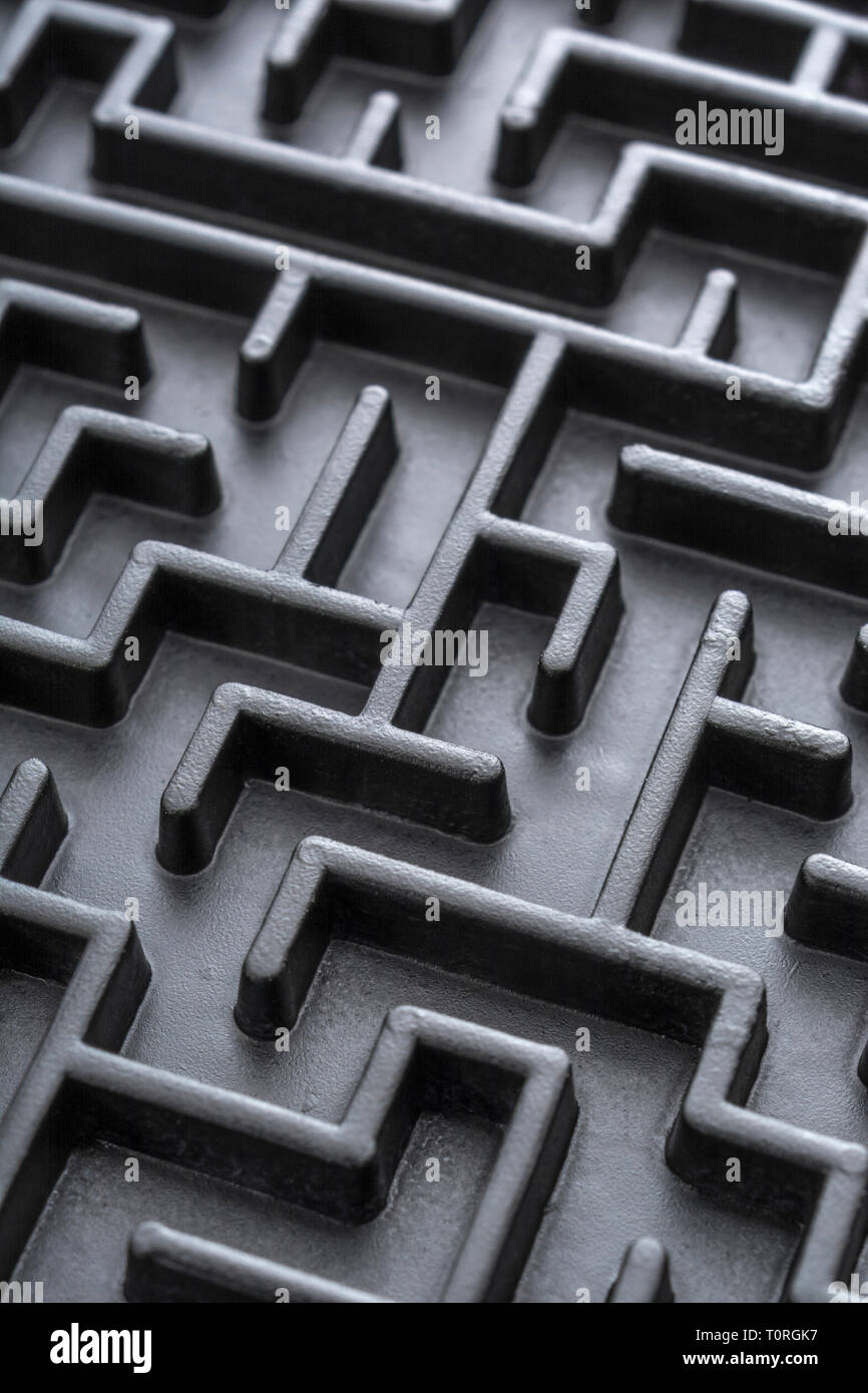 Macro shot of small toy maze painted black  Metaphor for complex