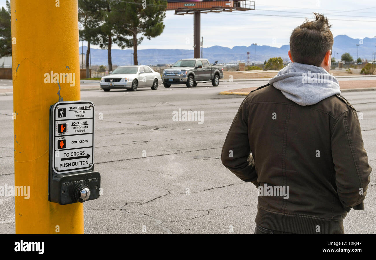 LAS VEGAS, NV, USA - FEBRUARY 2019: Person waiting to cross a road in Las Vegas alongside a push button operating panel for a pedestrian road crossing - Stock Image
