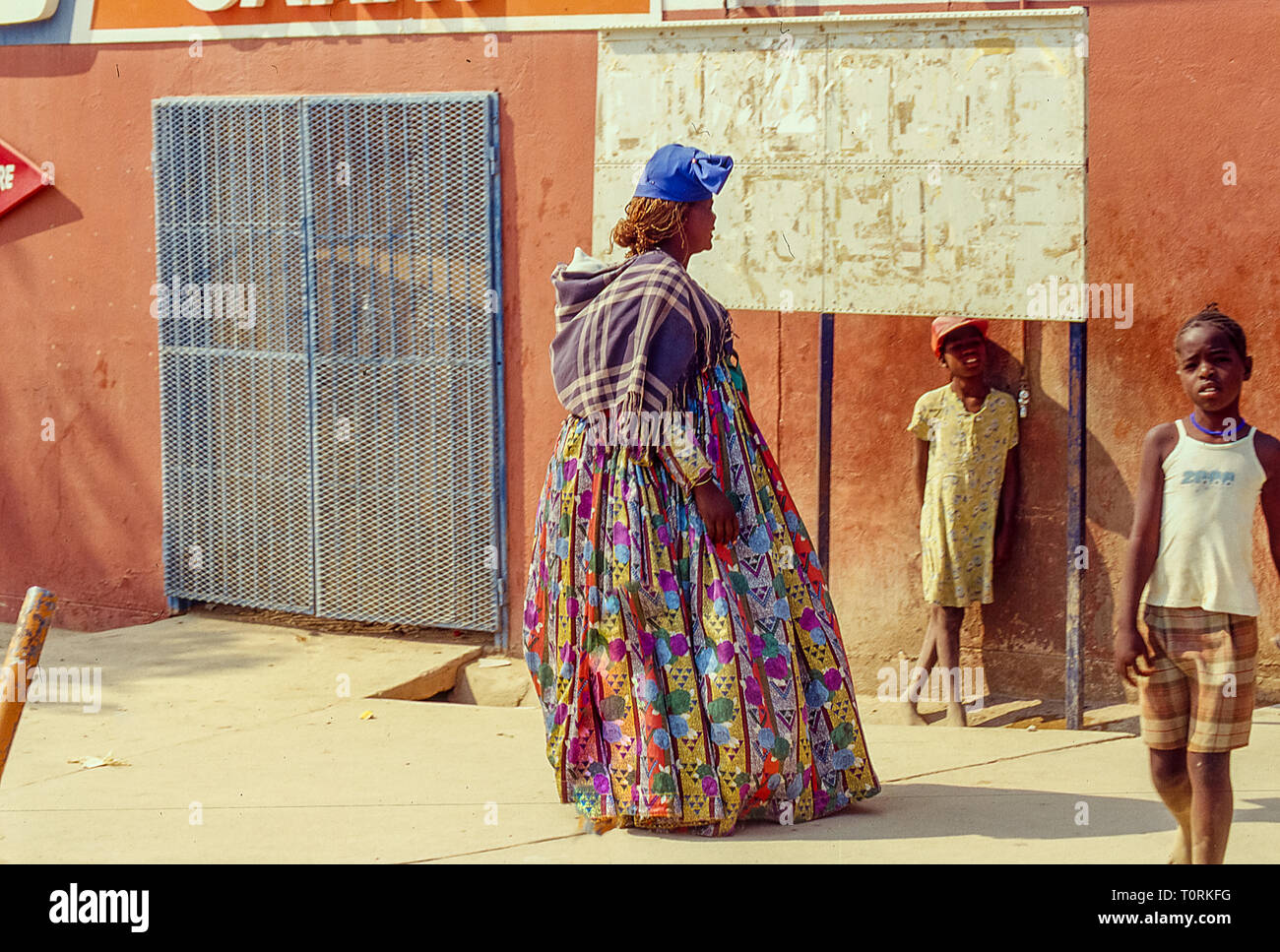 A woman of the Herero ethnicity with the traditional dress in the town of Opuwo in Namibia - Stock Image