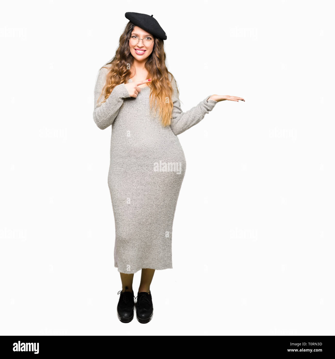 44b74579da403 Beautiful young woman wearing glasses and fashion beret amazed and smiling  to the camera while presenting
