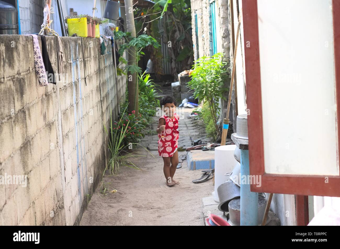 Ari Atoll, Maldives - 24 December 2018: A child with a red dress is playing outdoor - Stock Image
