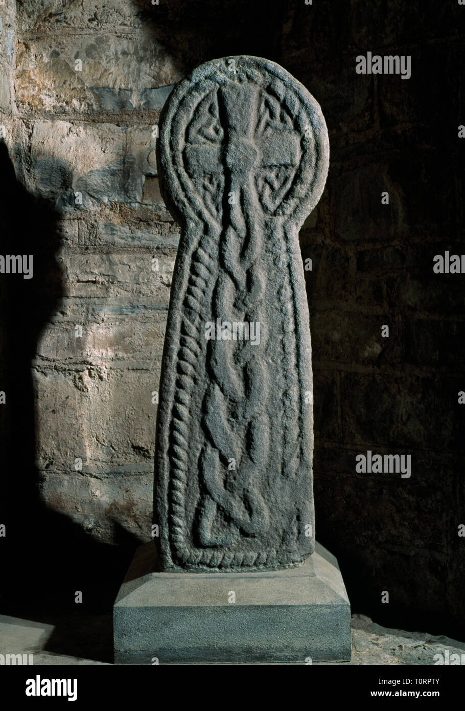 Laugharne church, Carmarthenshire, Wales, UK: a C10th round-headed cross-slab found in the churchyard & placed in the E wall of the south transept. - Stock Image