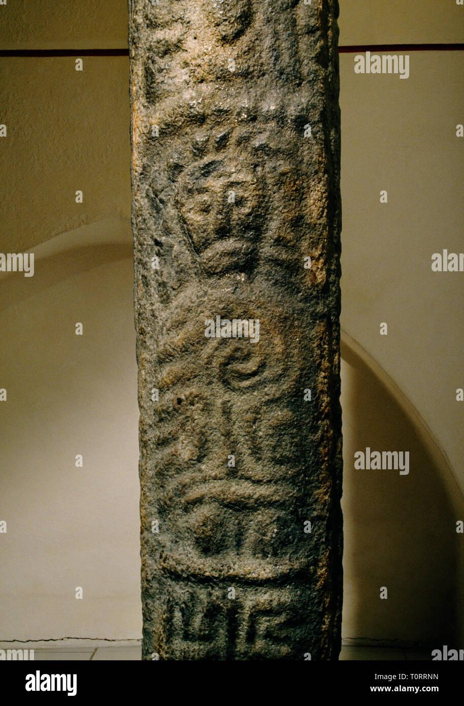 St Padarn's Cross: figure of a saint on front of C10th pillar cross in south transept museum of Llanbadarn Fawr parish church, Ceredigion, Wales, UK. - Stock Image